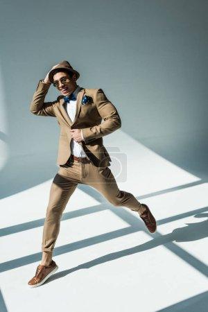 élégant mixte homme en costume souriant et sautant sur gris avec la lumière du soleil