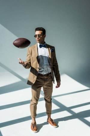 Photo for Stylish mixed race man in suit throwing soccer ball on grey with sunlight - Royalty Free Image
