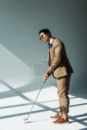 Photo for Stylish mixed race man in suit holding golf club on grey with sunlight - Royalty Free Image