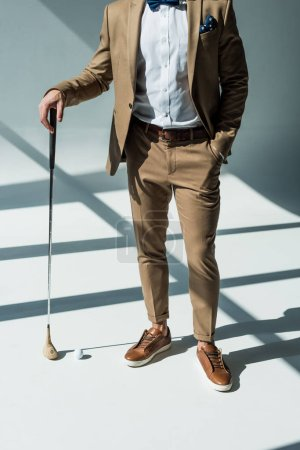 Photo for Cropped view of stylish mixed race man in suit posing with golf club on grey with sunlight - Royalty Free Image