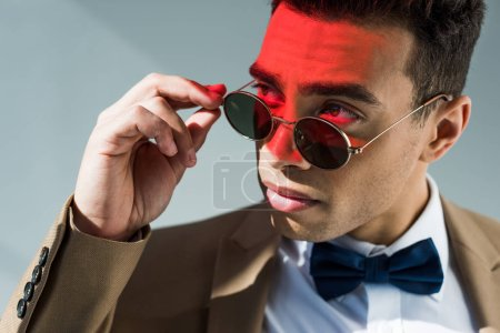 Photo for Stylish mixed race man in suit and sunglasses posing on grey with red light - Royalty Free Image