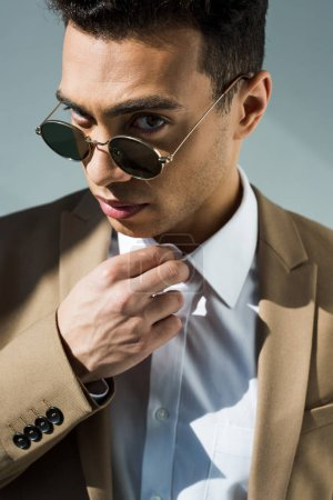 stylish mixed race man in suit and sunglasses adjusting shirt and looking at camera on grey