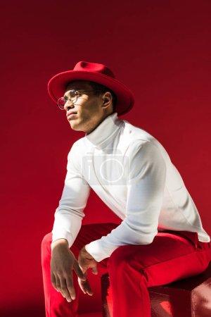 Photo pour Homme de race mixte à la mode dans le chapeau et les lunettes assis et posant isolé sur rouge - image libre de droit