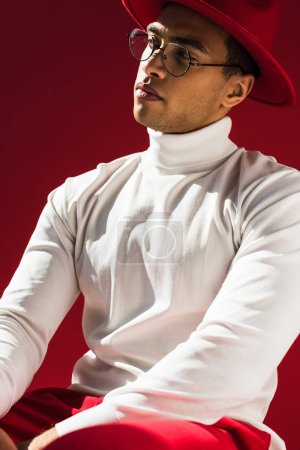 selbstbewusster, stylischer Mischlingsmann mit Hut und Brille posiert isoliert auf Rot