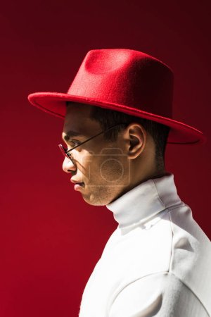 Photo for Side view of stylish mixed race man in hat and glasses posing isolated on red - Royalty Free Image