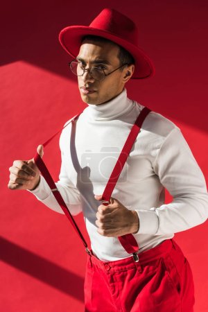fashionable mixed race man in hat and suspenders looking at camera while posing on red