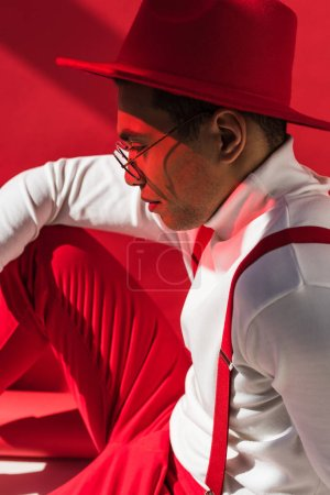 Photo for Side view of fashionable mixed race man in hat and suspenders posing on red - Royalty Free Image