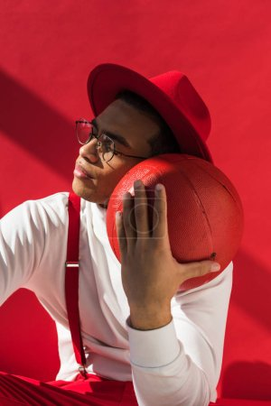 stylish mixed race man in hat and suspenders posing with basketball on red