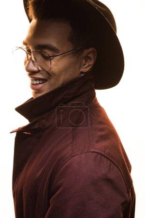 stilvoller Mischlingsmann mit Brille und Hut, der lächelt und isoliert auf weißem Grund posiert