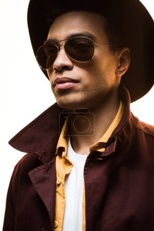 Photo for Stylish mixed race man in sunglasses and hat posing isolated on white - Royalty Free Image