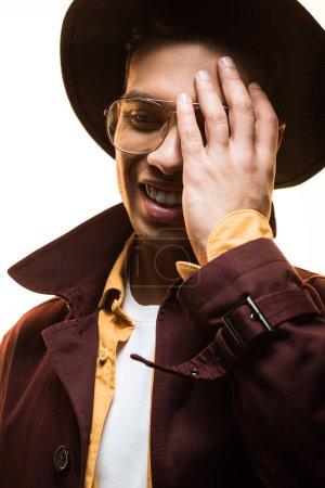 élégant homme de race mixte dans le chapeau et les lunettes couvrant le visage avec la main et souriant isolé sur blanc
