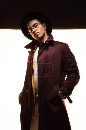 élégant mixte homme en chapeau et lunettes de soleil posant sur noir et blanc