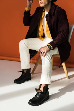 Photo for Cropped view of stylish mixed race man sitting and posing on orange - Royalty Free Image