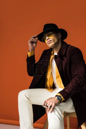 stylish mixed race man in hat and sunglasses sitting and posing on orange