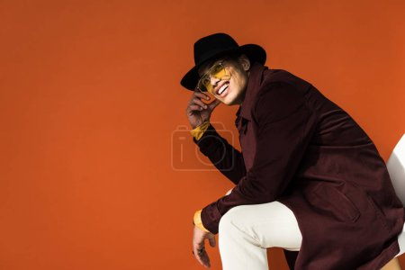 Photo for Stylish mixed race man in hat and sunglasses sitting and looking at camera isolated on orange with copy space - Royalty Free Image