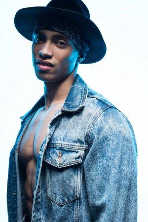 Foto de Apuesto hombre de raza mixta en denim y sombrero mirando cámara aislada en blanco - Imagen libre de derechos