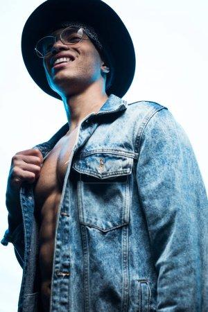 Tiefansicht eines hübschen gemischten Mannes in Jeans und Hut, der isoliert auf weißem Grund lächelt