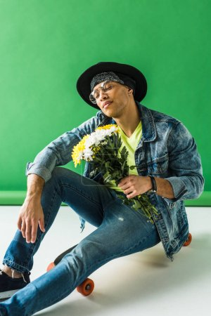 stylish mixed race man in denim sitting on skateboard with flowers and posing on green