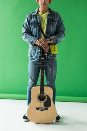 Photo pour Vue recadrée de l'homme de course mixte en denim posant avec la guitare acoustique sur le vert - image libre de droit