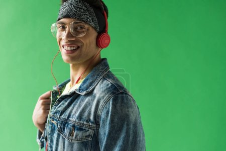 Foto de Hombre de raza mixta guapo en auriculares mirando a la cámara y sonriendo mientras escucha música en la pantalla verde - Imagen libre de derechos
