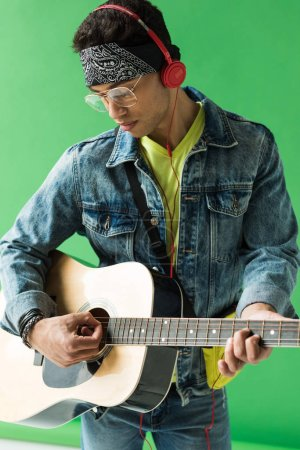Photo for Handsome mixed race man in denim and headphones playing acoustic guitar on green - Royalty Free Image