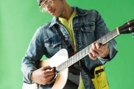 Photo for Selective focus of mixed race man in denim playing acoustic guitar on green screen - Royalty Free Image