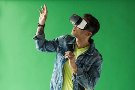 Photo for Mixed race man in vr headset gesturing while experiencing virtual reality on green screen - Royalty Free Image