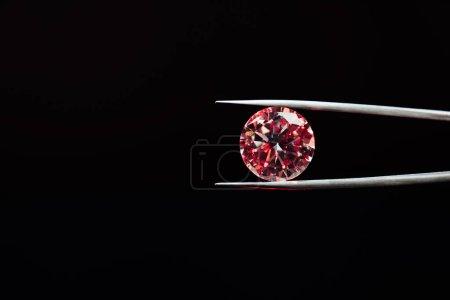 Photo pour Diamant étincelant rouge coloré dans des pinces isolées sur noir - image libre de droit