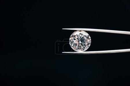 Foto de Diamante brillante puro transparente en pinzas aisladas en negro - Imagen libre de derechos