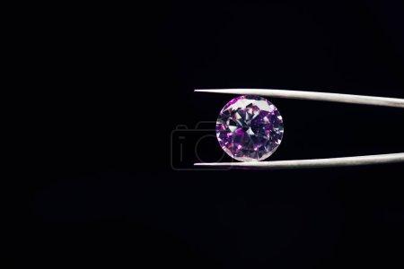 Foto de Colorido diamante brillante púrpura en pinzas aisladas en negro - Imagen libre de derechos