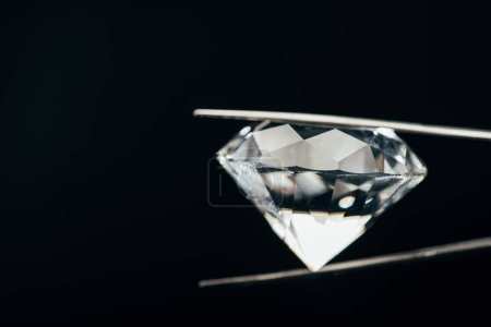 Photo for Transparent pure sparkling diamond in tweezers isolated on black - Royalty Free Image