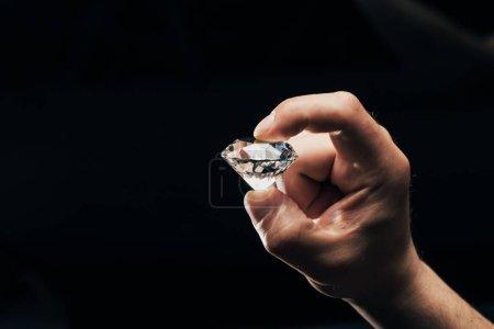 Photo pour Vue partielle de l'homme tenant gros diamant clair brillant isolée sur fond noir - image libre de droit