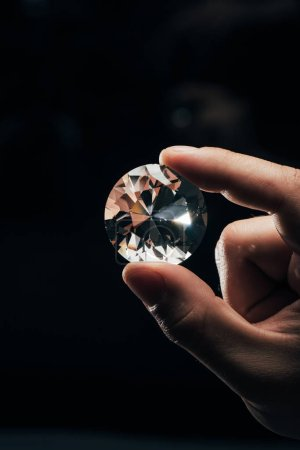 Photo for Cropped view of man holding big clear shiny diamond on black background - Royalty Free Image
