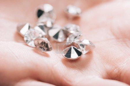 Photo pour Gros plan de brillants petits diamants purs dans la main - image libre de droit