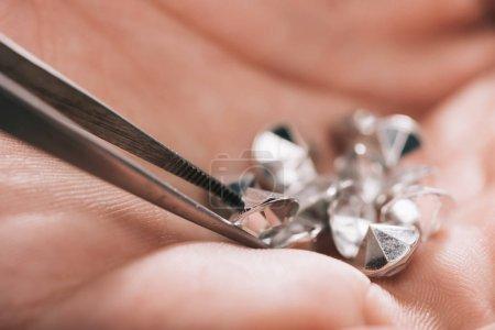 Photo pour Gros plan de pincettes près de diamants brillants dans la main - image libre de droit