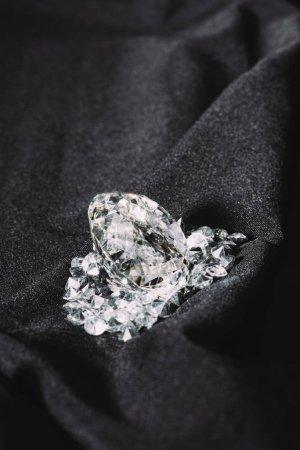 Photo pour Tas de brillants diamants purs sur tissu texturé noir - image libre de droit