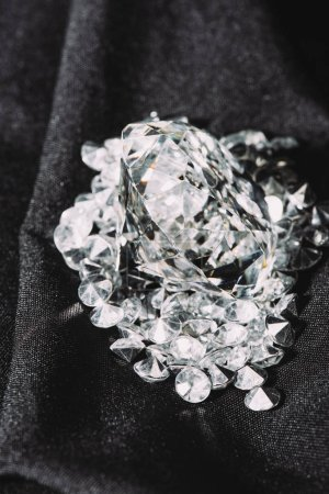 pile of sparkling pure diamonds on black shiny cloth