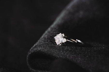 Photo pour Bague de fiançailles avec diamant brillant pur sur tissu noir - image libre de droit