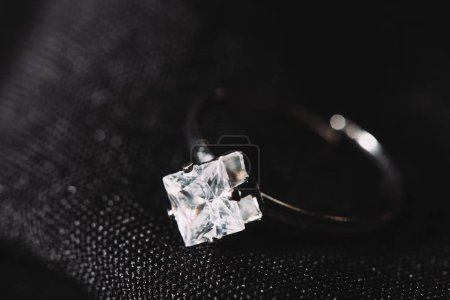 Photo pour Bague de fiançailles avec diamant étincelant pur sur tissu noir - image libre de droit