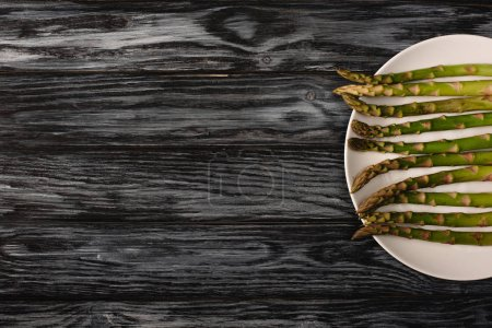 top view of green organic asparagus on plate on grey wooden background with copy space