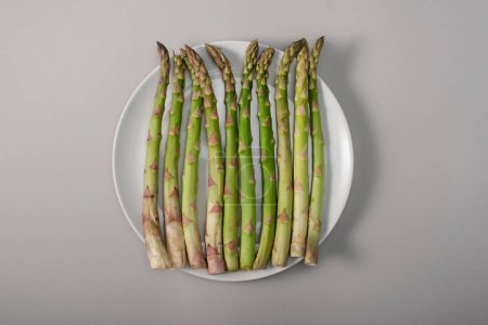 top view of green organic asparagus on plate on grey background