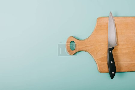 Photo for Top view of wooden cutting board with knife on blue background with copy space - Royalty Free Image
