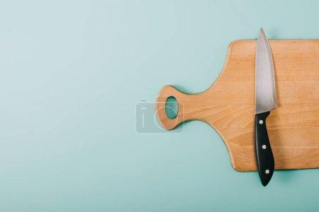Photo pour Vue de dessus de la planche à découper en bois avec couteau sur fond bleu avec espace copie - image libre de droit