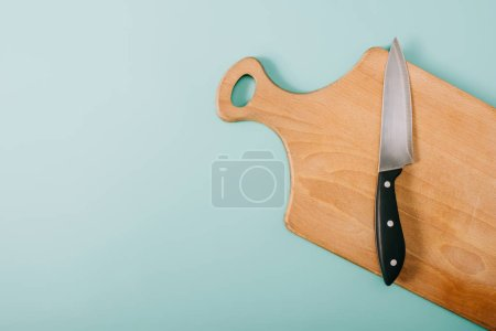 Photo for Top view of wooden cutting board with knife on blue background - Royalty Free Image