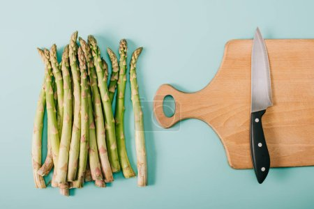 Photo for Top view of green raw asparagus near wooden cutting board with knife on blue background - Royalty Free Image