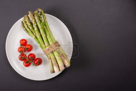Photo for Top view of green asparagus and cherry tomatoes on plate on black background - Royalty Free Image