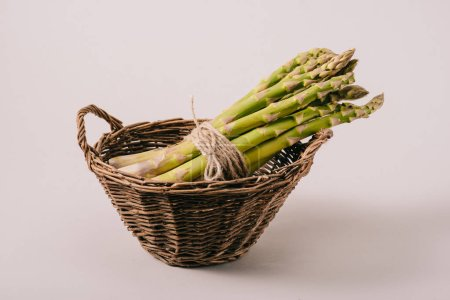 Photo for Bunch of green uncooked asparagus tied with rope in wicker basket on grey background - Royalty Free Image