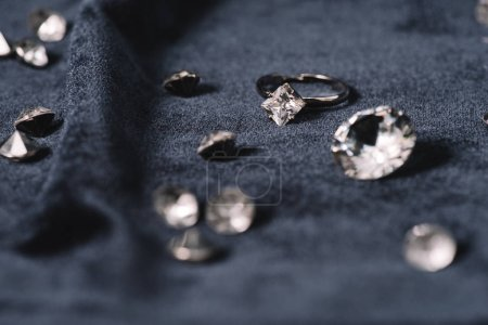 Photo pour Foyer sélectif de bague de fiançailles près de diamants brillants sur tissu bleu - image libre de droit