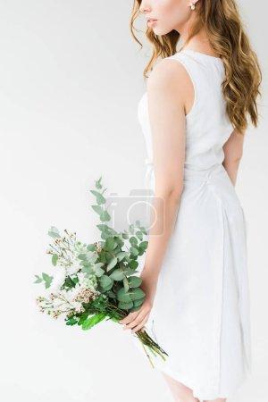 Photo pour Vue recadrée de femme en robe élégante retenant des fleurs d'isolement sur le blanc - image libre de droit