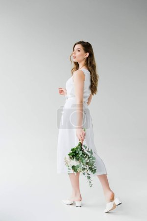 Photo for Attractive girl in dress walking with flowers on grey - Royalty Free Image